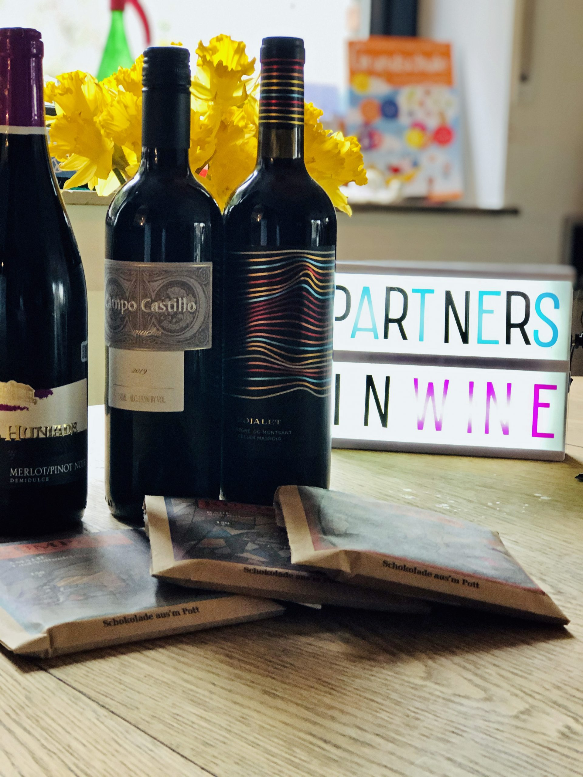 Drei Flaschen Wein und drei Tafeln Kumpelschokolade