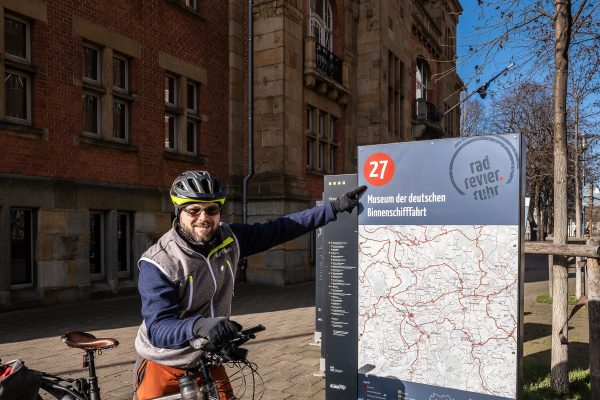 Das Foto zeigt einen Radfahrer am Knotenpunkt 27, dem Museum der deutschen Binnenschifffahrt in Duisburg