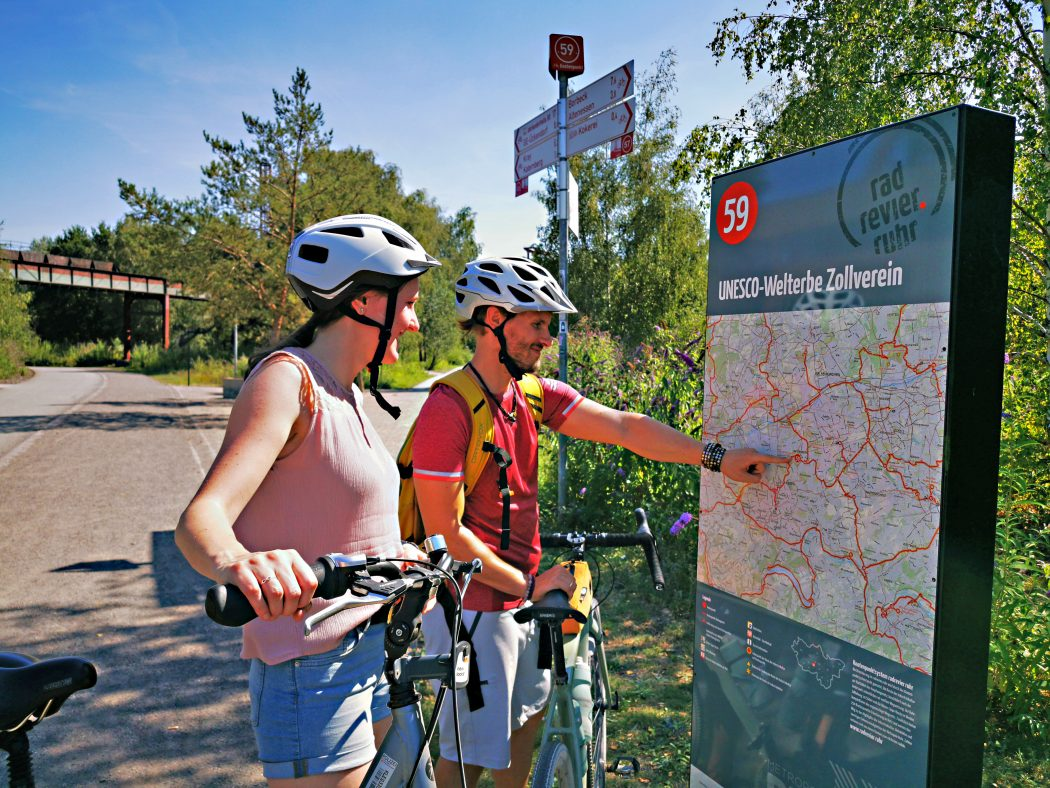Das Foto zeigt zwei Radfahrer an einer Übersichtskarte des Knotenpunktsystems im Ruhrgebiet