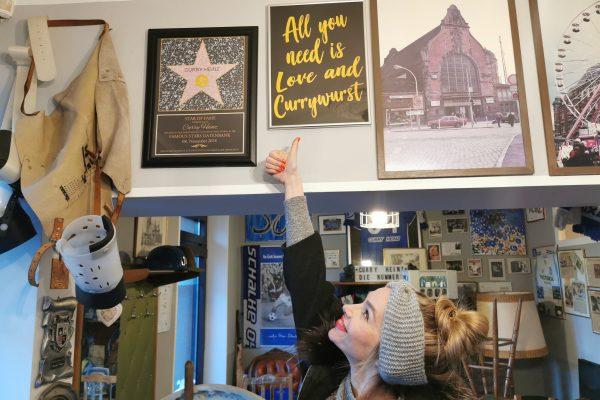 """Das Foto zeigt Sandra vor einem Bild mit der Message """"All you need is Love and Currywurst"""" beim Curry Heinz in Gelsenkirchen"""
