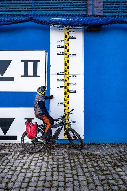 Das Foto zeigt einen Radfahrer an den Hochwassermarkierungen des Rheins in Duisburg