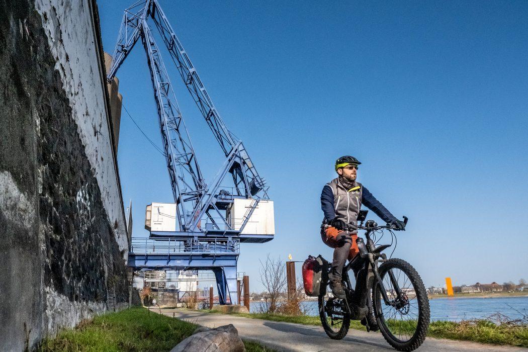 Das Foto zeigt einen Radfahrer am Rhein - hinter ihm ein Kran und die Rheinorange in Duisburg