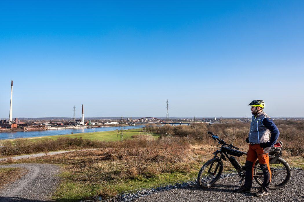 Das Foto zeigt einen Radfahrer auf dem Rockelsberg mit Aussicht auf den Rhein bei Duisburg