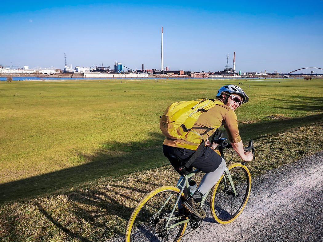 Das Foto zeigt einen Radfahrer auf dem Rheindamm in Duisburg
