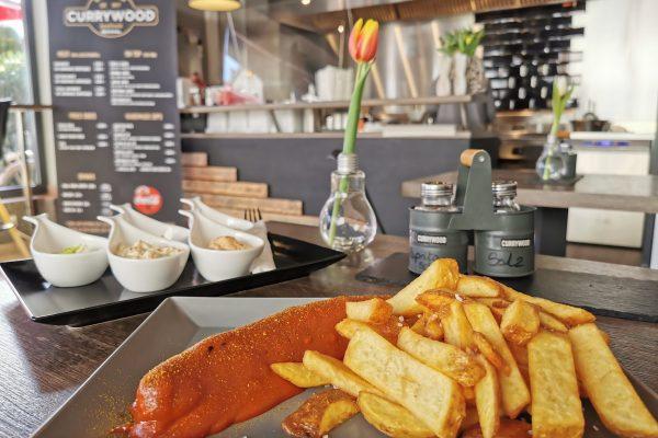 Das Foto zeigt Currywurst mit Pommes und Dips im Currywood in Bottrop