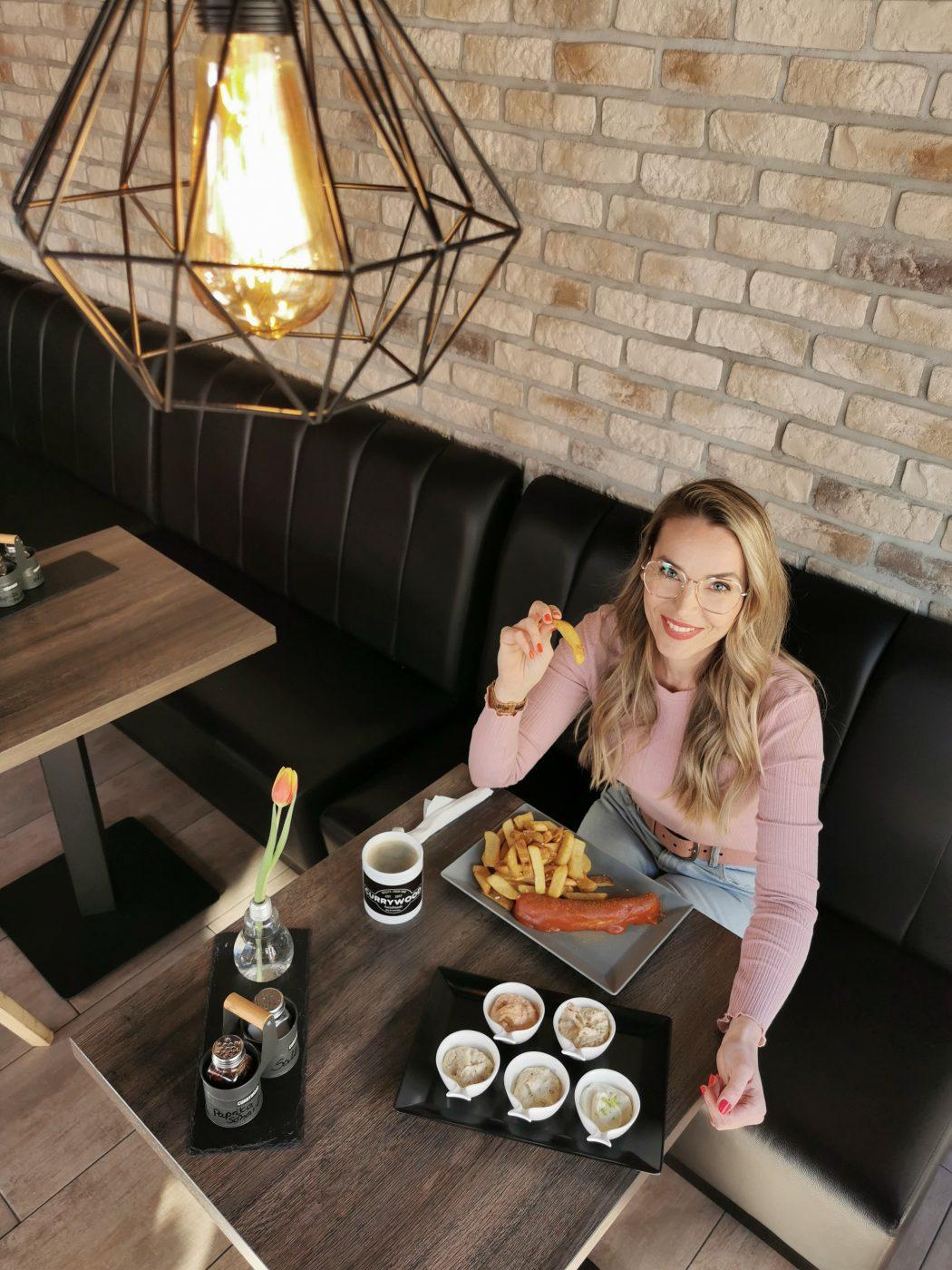 Das Foto zeigt Sandra mit Currywurst im Currywood in Bottrop