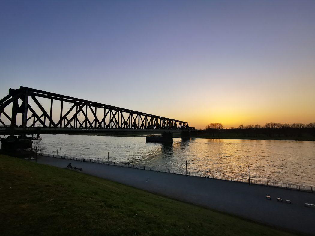 Das Foto zeigt die markante Eisenbahnbrücke in Duisburg-Wanheimerort bei Sonnenuntergang