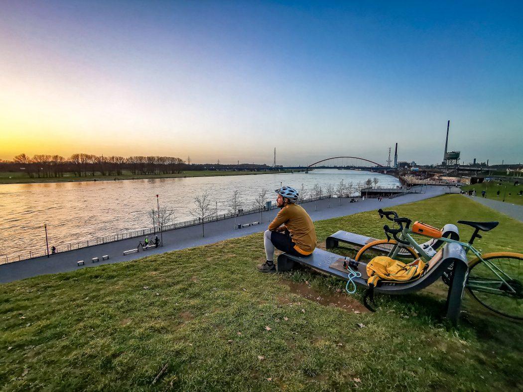 Das Foto zeigt einen Radfahrer mit Blick auf den Sonnenuntergang am Rhein in Duisburg