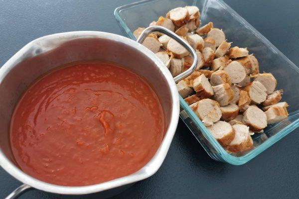 Das Foto zeigt geschnittene Bratwurst und Sauce