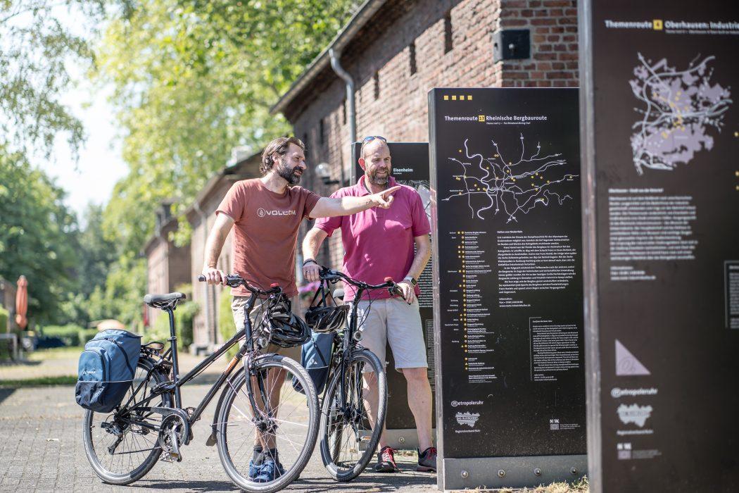 Das Foto zeigt zwei Radfahrer an den Info-Brammen der Route Industriekultur an der Arbeitersiedlung Eisenheim in Oberhausen