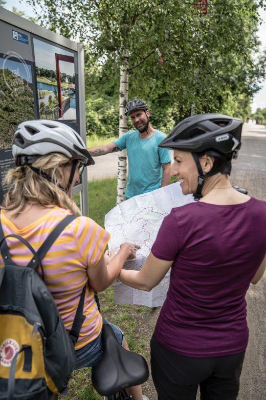 Das Foto zeigt Radfahrer im Ruhrgebiet mit einer Radkarte des radrevier.ruhr
