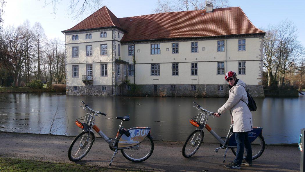 Das Foto zeigt eine Radfahrerin und zwei Fahrräder am Schloss Strünkede in Herne