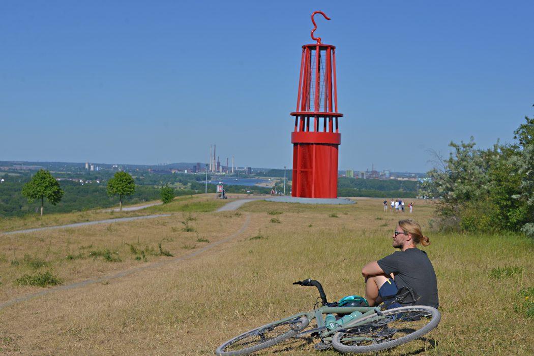 Das Foto zeigt einen Radfahrer auf der Halde Rheinpreußen mit dem Geleucht in Moers