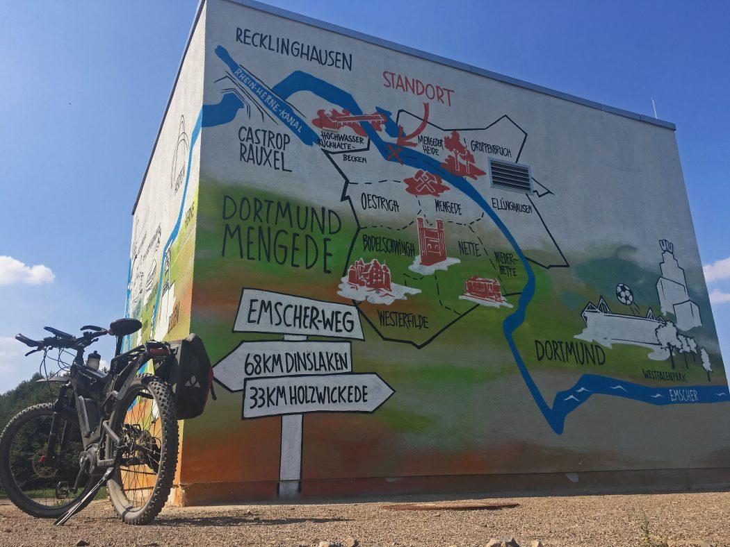 Das Foto zeigt ein Fahhrad vor einem Graffiti des Emscher-Weges