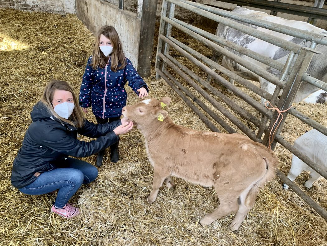 Das Foto zeigt Nina und ihre Tochter mit einem Kälbchen auf dem Bauernhof Sagel in Bottrop-Kirchhellen
