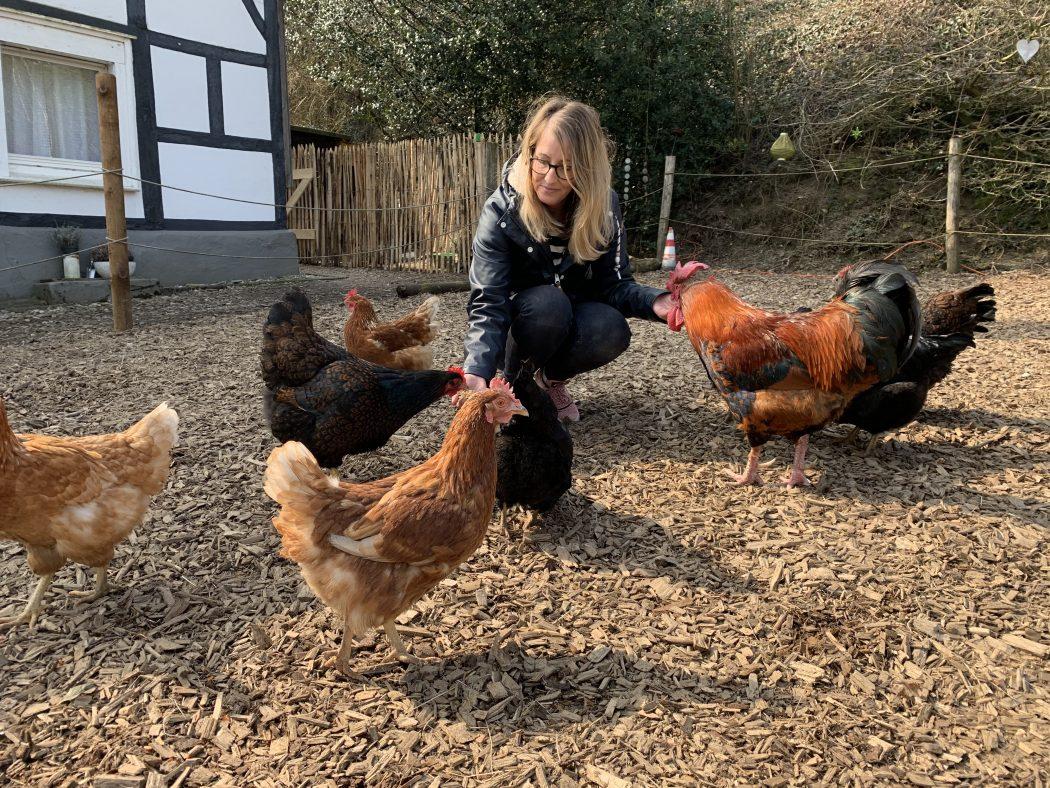 Das Foto zeigt Nina mit einigen Hühnern auf dem Begegnungshof in der Espe mitten in der Elfringhauser Schweiz