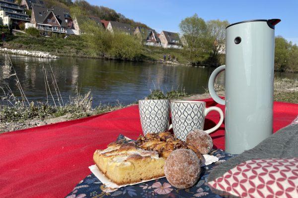 Das Foto zeigt Kaffee und Kuchen am Ruhrufer in Hattingen - ein perfekter Ort für ein Picknick im Ruhrgebiet