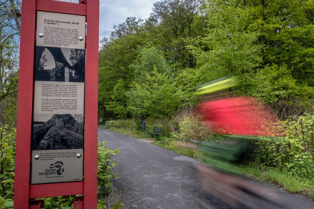 Das Foto zeigt eine Infotafel am Wegesrand der Niederbergbahntrasse in Essen-Kettwig