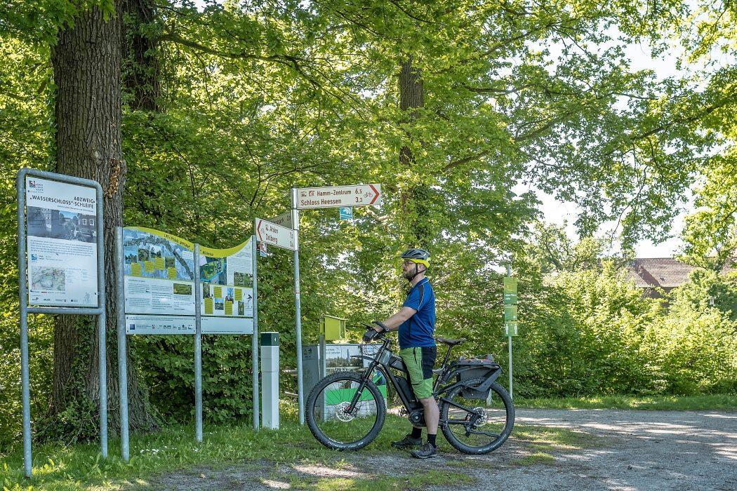 Das Foto zeigt Jochen vor Wegweisern des rot-weißen Radverkehrsnetzes