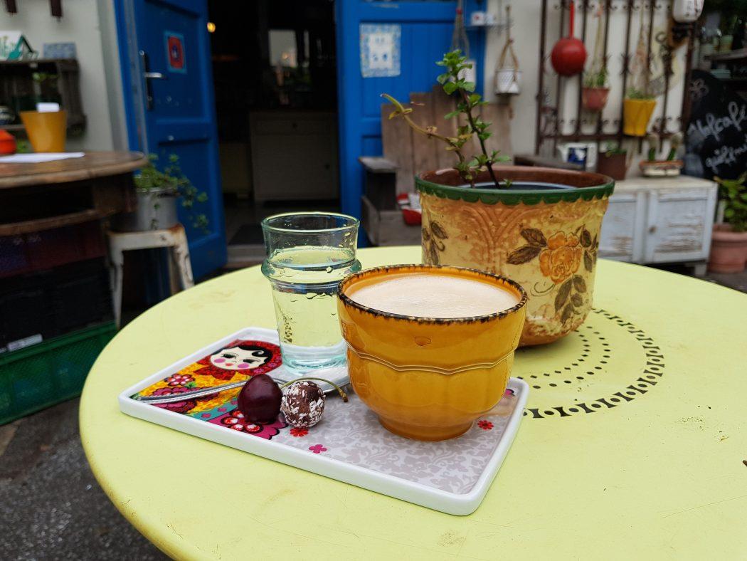 Das Foto zeigt einen Cappuccino und Wasser im Hof des Hofcafés in Dortmund