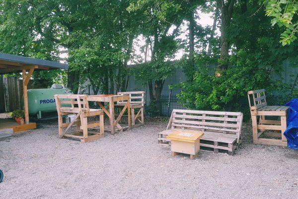 Das Foto zeigt die selbstgemachten Altholzmöbel im Hinterhof der Kaffeerösterei three years one day in Bochum