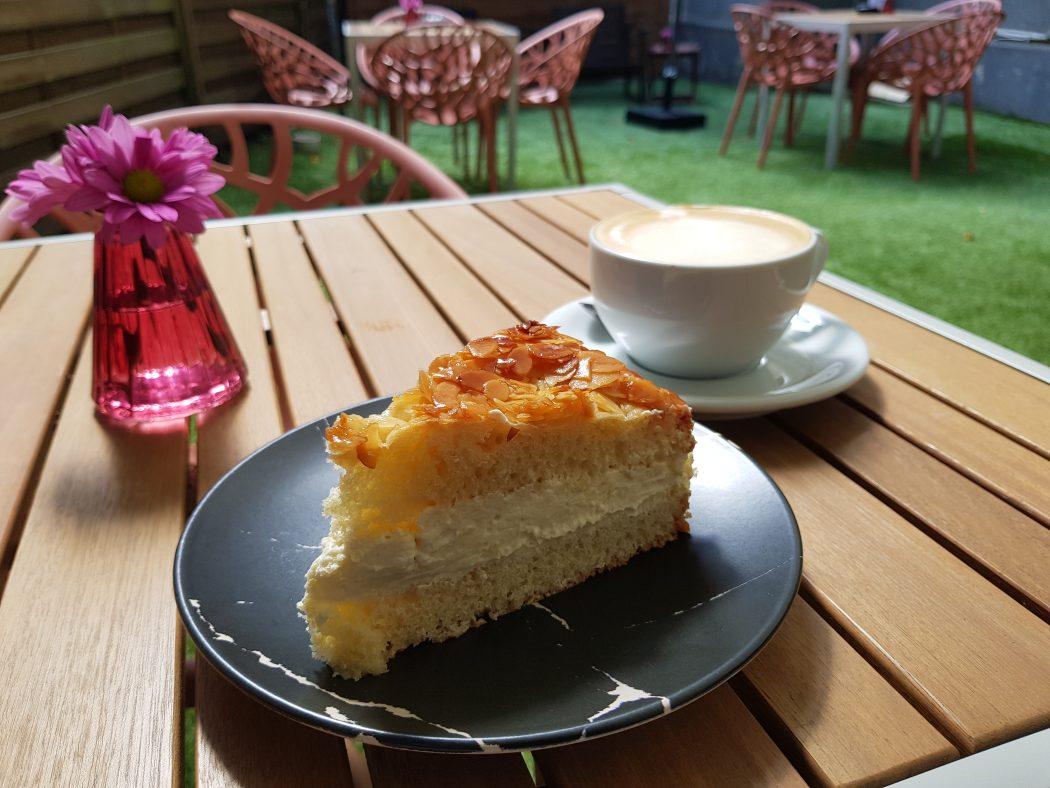 Das Foto zeigt veganen Bienenstich im gemütlichen Hinterhof des Café Rot in Dortmund