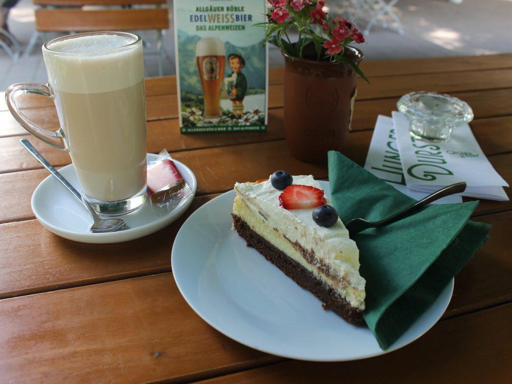 Das Foto zeigt Brownie-Cheesecake und Chai-Latte im Biergarten des Grünen Salons in der Nordstadt von Dortmund