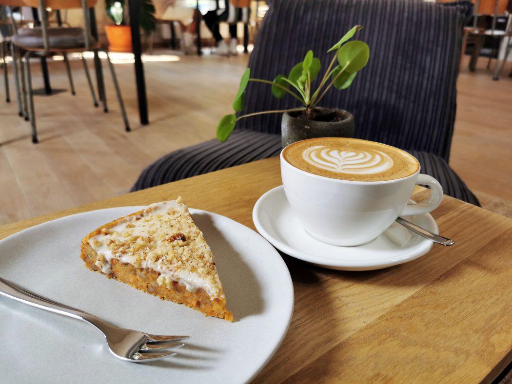 Das Foto zeigt Karotte-Walnuss-Kuchen und Cappuccino im STÜH33 in Bochum