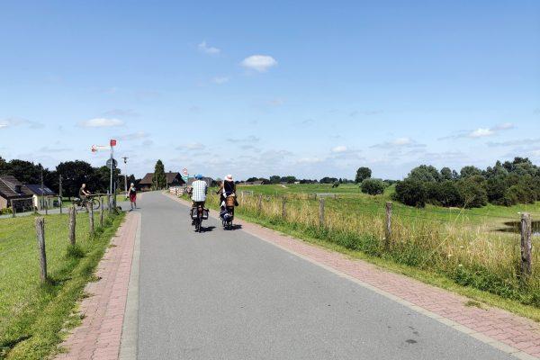 """Das Foto zeigt zwei Radfahrer auf dem Rheindamm in Xanten, der oberhalb des """"Unser Lieblingscafé"""" verläuft"""