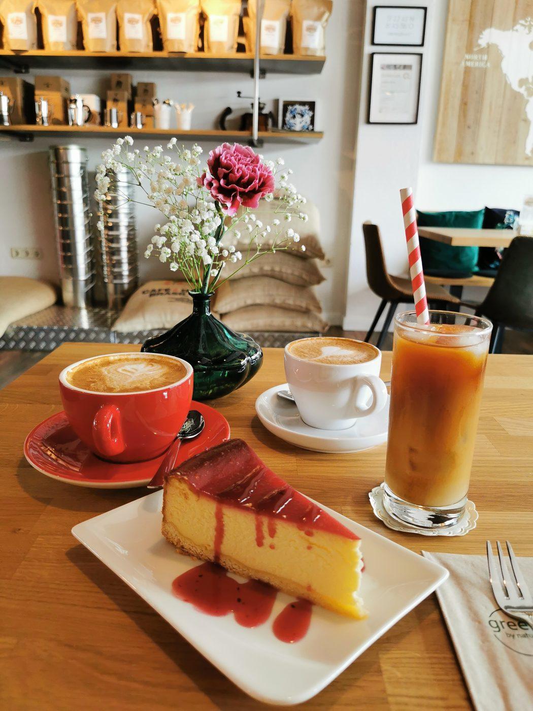 Das Foto zeigt Käsekuchen, Cappuccino und Cold Brew der Kaffeerösterei RöstCult in Duisburg