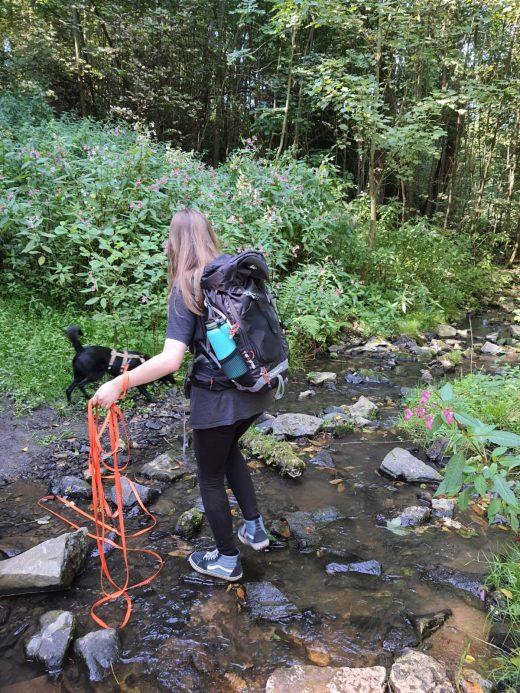 Das Foto zeigt Melissa mit ihrem Hund an einem Bach auf dem Kettwiger Panoramasteig