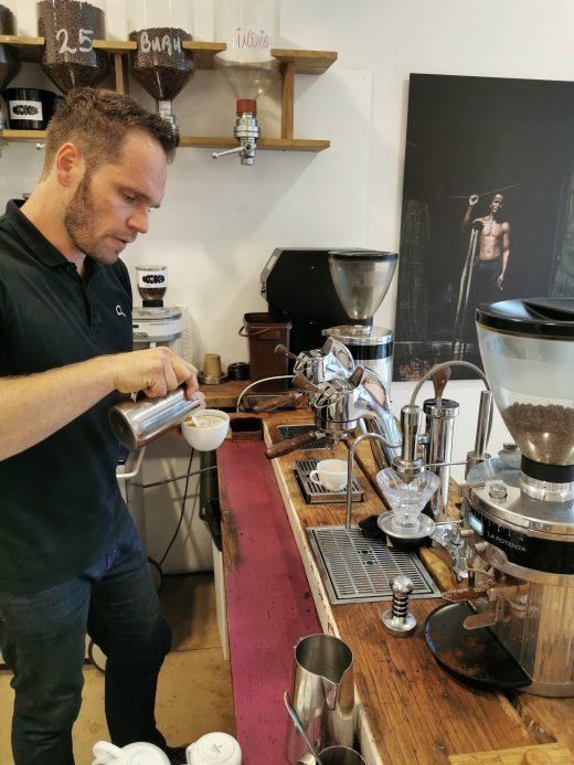 Das Foto zeigt Simon, den Betreiber der Kaffeerösterei Bristoteles in Bochum, bei der Zubereitung eines Cappuccinos
