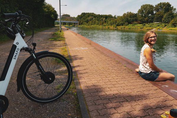 Das Foto zeigt Christin mit Fahrrad am Rhein-Herne-Kanal