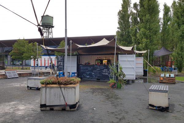 Das Foto zeigt die Die Pappelwaldkantine mit Foodtruck und Sitzgelegenheiten bei der Ruhrtriennale an der Jahrhunderthalle Bochum