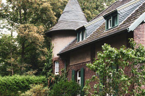 Das Bild zeigt ein Eckhaus mit Turm in der Siedlung Rheinpreußen
